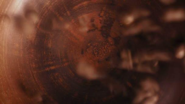 Detail, pohled shora kávová zrna spadají do hliněné desky