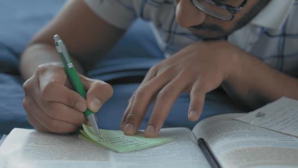 Close-up, indický student ve skleničkách dělá záznamy v postýlce ležící na posteli