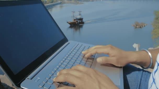 Close-Up, indiai diák Hands Type laptop billentyűzet szöveg a háttérben a hajó vitorlázás a folyón