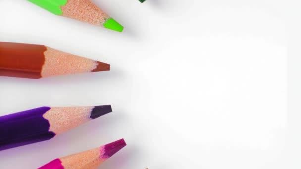 Zavřít, pohled shora, řádek barevných tužek pomalu otočit kolem kruhu vlevo na bílém stole