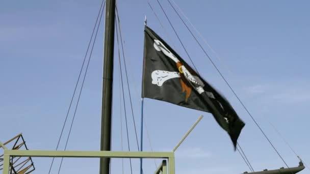 Pirate Black Flag, Jolly Roger, Flutters nel vento vicino allalbero di una nave ormeggiata