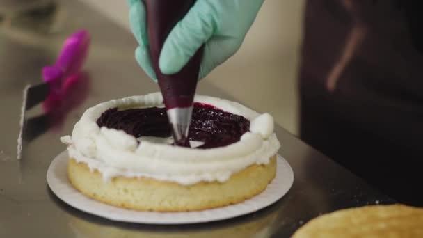 Detailní záběr, pečivo vymačkává ovocnou marmeládu na dort z tašky cukrovinek