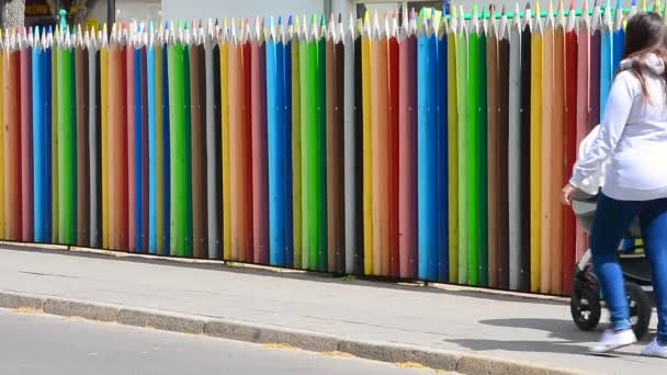 Two woman walk along a colourful fence at a pre-school in Swinoujscie, Poland,  May 14, 2016