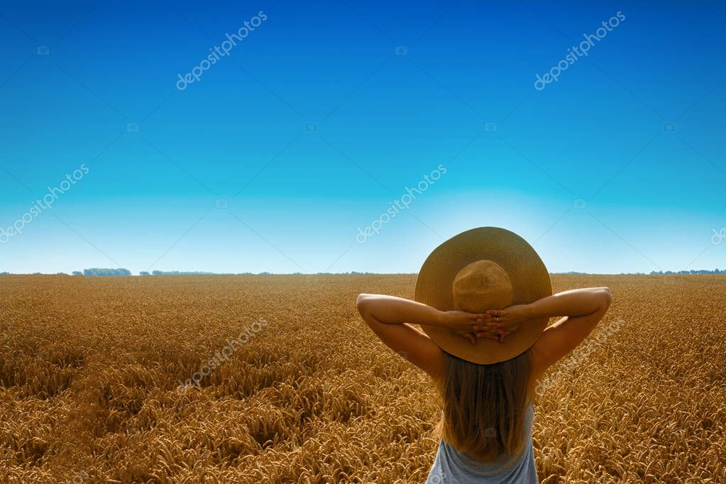 Young pretty blond girl happy looking at the sun in the zenith. She is wearing a hat. Transmission field. Back view.