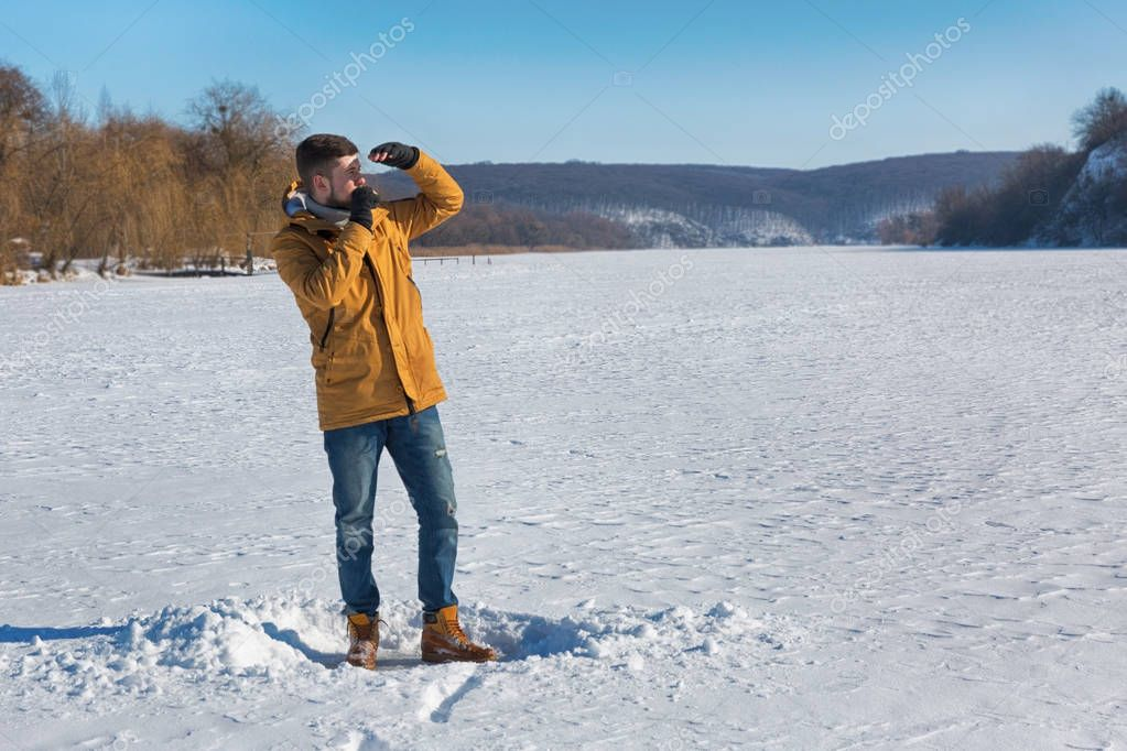 Vaper man standing in winter day and smoking e-cigarette