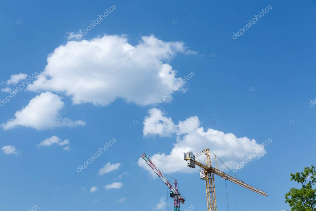 Two tower cranes against a sunny sky with white clouds.