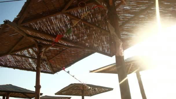 dekorierte Strohschirme am windigen Morgen am Strand, Himmel im Hintergrund