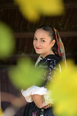 Young beautiful slovak woman in traditional costume. Autumn portrait.