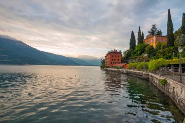 holidays in Italy - a view of a city Bellano, with the most  beautiful lake in Italy - Lago di Como in background. Area of famous Belano City at sunset