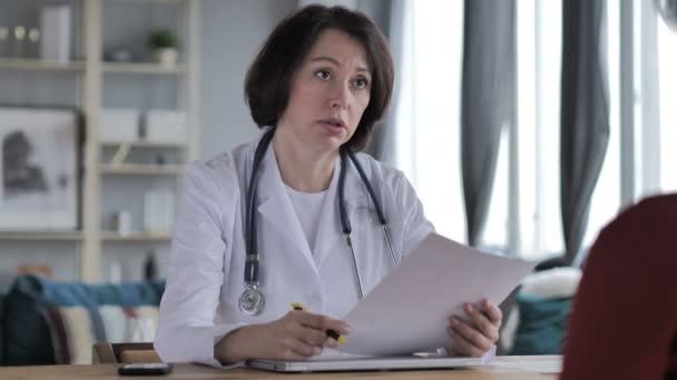 Stará paní doktor diskusi léčby s pacientem v klinice
