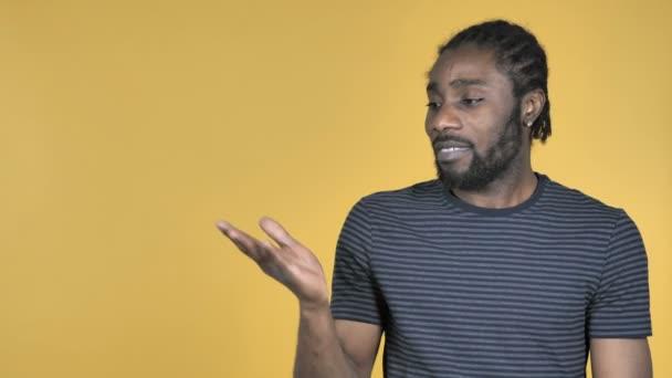 Příležitostné africký muž zobrazeno produktu na straně, žluté pozadí