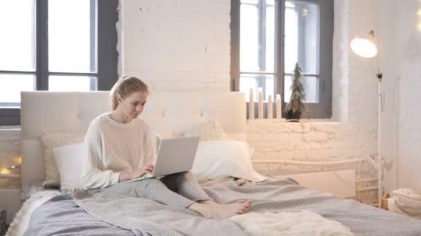 erstaunt junges Mädchen überrascht von Ergebnissen auf Laptop im Bett