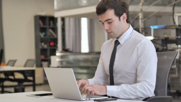 Smiling Young Businessman Looking at Camera in Office