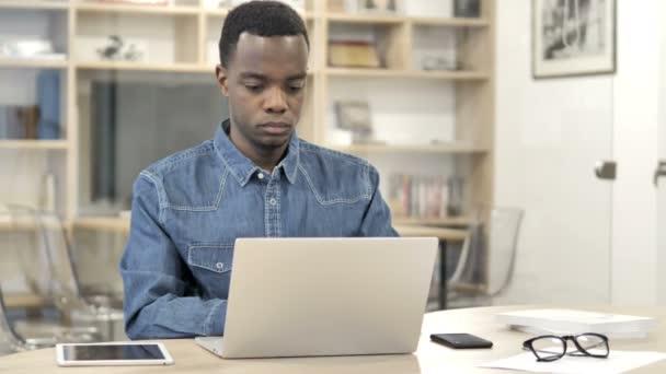 Afrikanischer Mann mit Nackenschmerzen arbeitet am Laptop