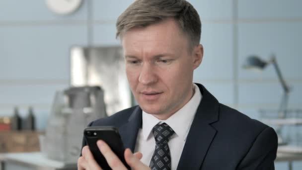 Obchodník oslavující úspěch na telefonu Smartphone