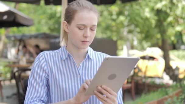 junge Frau sitzt mit Tablet auf Caféterrasse