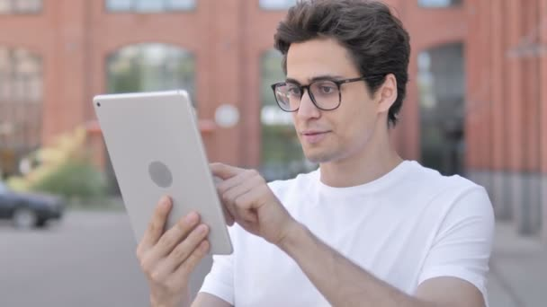 Outdoor Portrait of Young Man Celebrating Success on Tablet