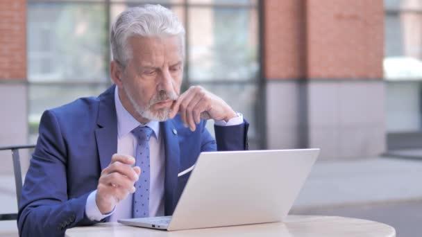 nachdenklicher alter Geschäftsmann mit Laptop, im Freien