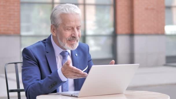 Online-Videochat auf dem Laptop von alten Geschäftsmann sitzt im Freien