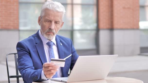 Erfolgreicher Online-Einkauf durch alten Geschäftsmann