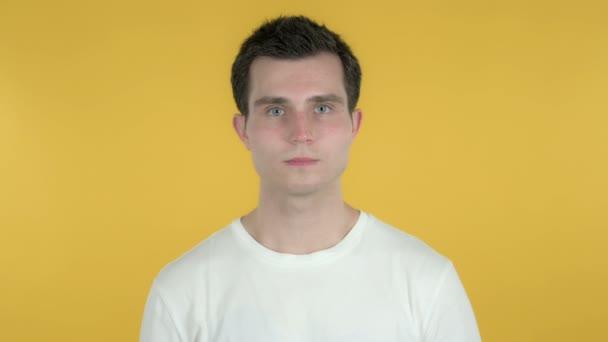 Mladý muž ukazující na fotoaparát izolovaný na žlutém pozadí