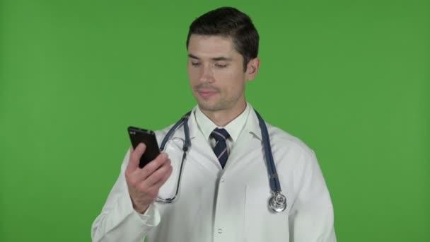 Mladý doktor používá hovor na mobil, chroma klíč