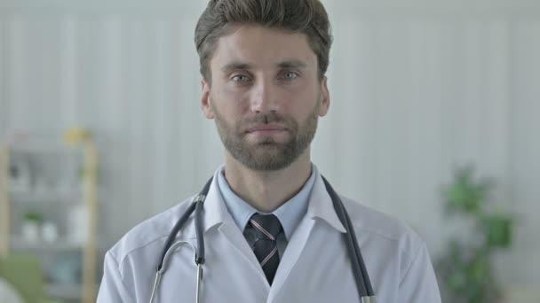 Veselý mladý lékař se usmívá na kameru