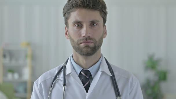 ernsthafter junger Arzt mit Bart blickt in die Kamera