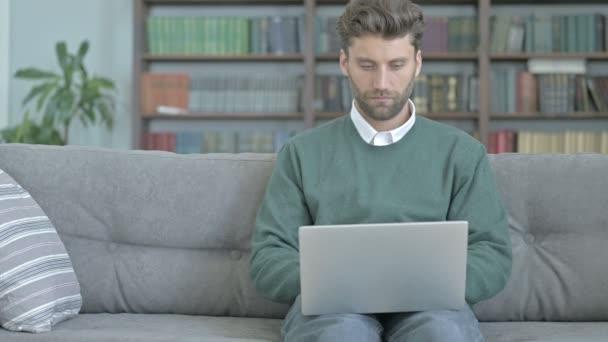 Vážný mladý muž sedící na pohovce a práce na přenosném počítači
