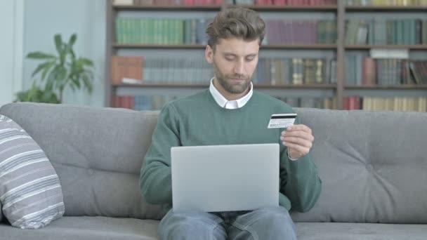 Mann sitzt auf Sofa und fügt Kreditkartendetails auf Laptop hinzu