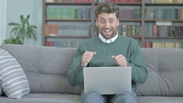 Mladý muž pocit poraženého při práci na přenosném počítači