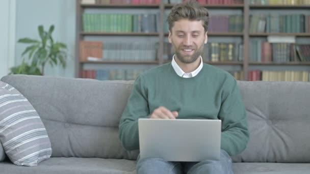 Mann sitzt auf Sofa und telefoniert per Laptop