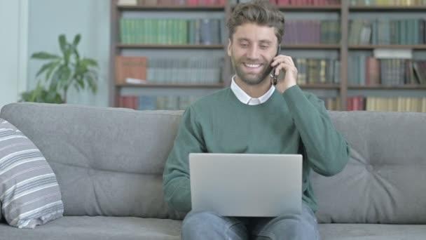 Úsměv mladého muže při telefonním hovoru a práci na přenosném počítači
