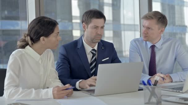 Executive Business people sharing Report through Laptop on Office Table