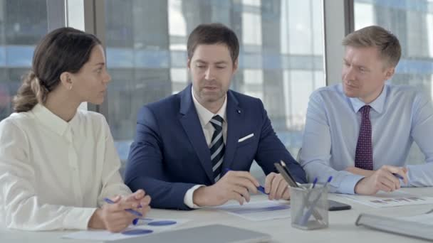 Középkorú üzletember, miután elmagyarázza a dolgokat, hogy az asszisztensek az Office táblázat