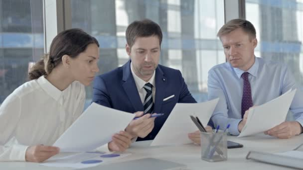 Middle Aged Businessman Discussion Documents with his Assistants on Office Table