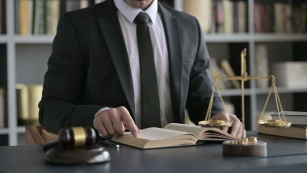 Close up Shoot of Lawyer Hand Reading Book on Court Room Table