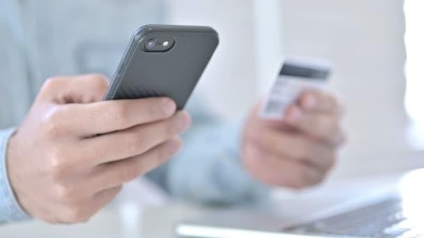 Nahaufnahme der Hände mit Kreditkarte auf dem Smartphone