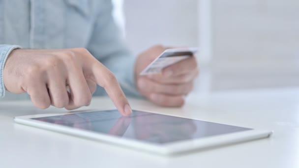 Fiatal kezek közeli felvétele hitelkártyával a Tablettán
