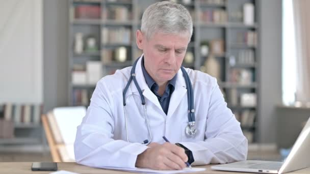 Profesionální senior lékař psaní na papírech, zatímco sedí v kanceláři