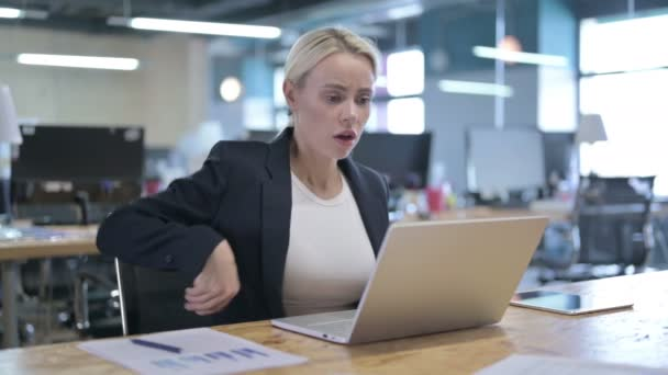 müde Geschäftsfrau mit Rückenschmerzen bei der Arbeit