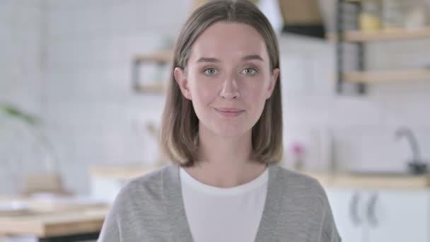 Porträt einer jungen Frau, die mit dem Finger auf die Kamera zeigt