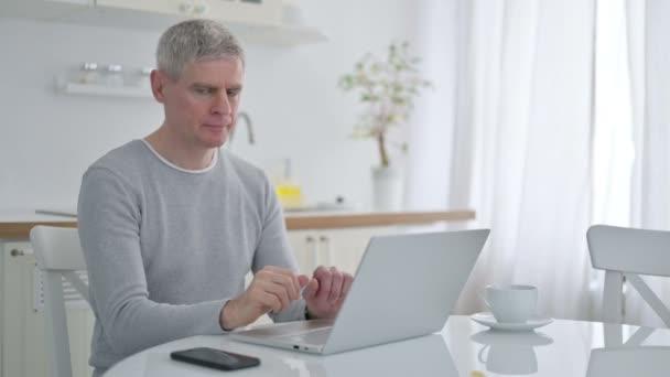 Positiver Senior mit Laptop zeigt Ja-Zeichen mit Finger
