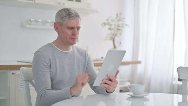 Älterer Mann bei Videochat auf Tablet zu Hause