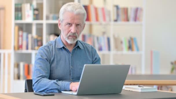 Älterer Mann mit Laptop aufgebracht und Daumen runter