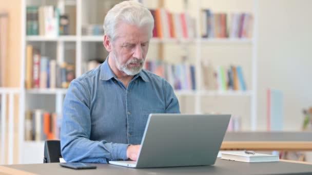Positiver älterer Mann mit Laptop macht Daumen hoch