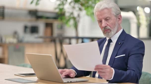 Älterer Geschäftsmann mit Laptop liest Dokumente