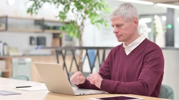 Schwerwiegender Mann mittleren Alters mit Laptop blickt in die Kamera
