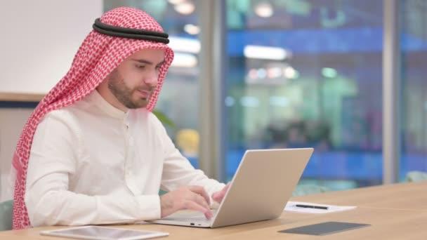 Glücklicher arabischer Geschäftsmann feiert Erfolg auf Laptop im Büro