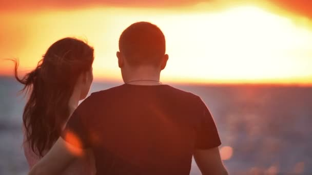 Young couple. Man and woman. Watching the sunset dawn. Admiring. They embrace. On the beach.